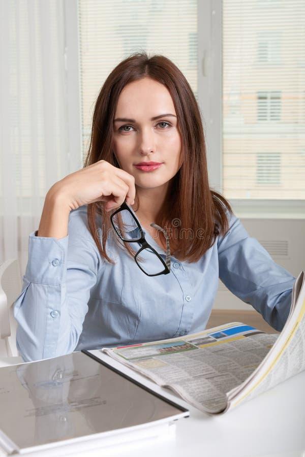 Kvinnasammanträde på tabellen i regeringsställning som in rymmer handen en tidning royaltyfri foto
