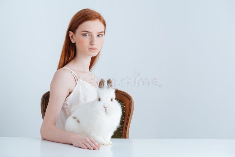 Kvinnasammanträde på tabellen med kanin arkivbilder