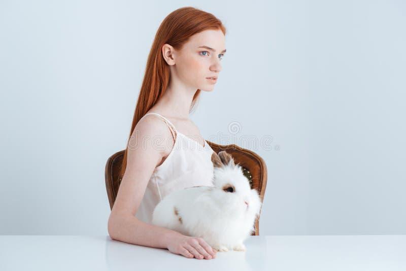Kvinnasammanträde på tabellen med kanin royaltyfria bilder