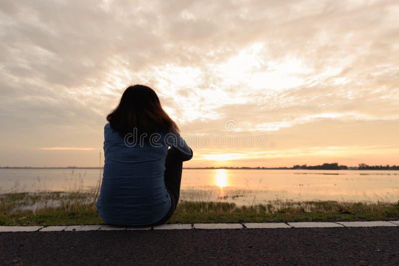 Kvinnasammanträde på vägrenen bredvid floden på solnedgången royaltyfri foto