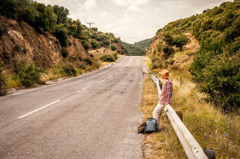 Kvinnasammanträde på vägstaketet royaltyfri fotografi