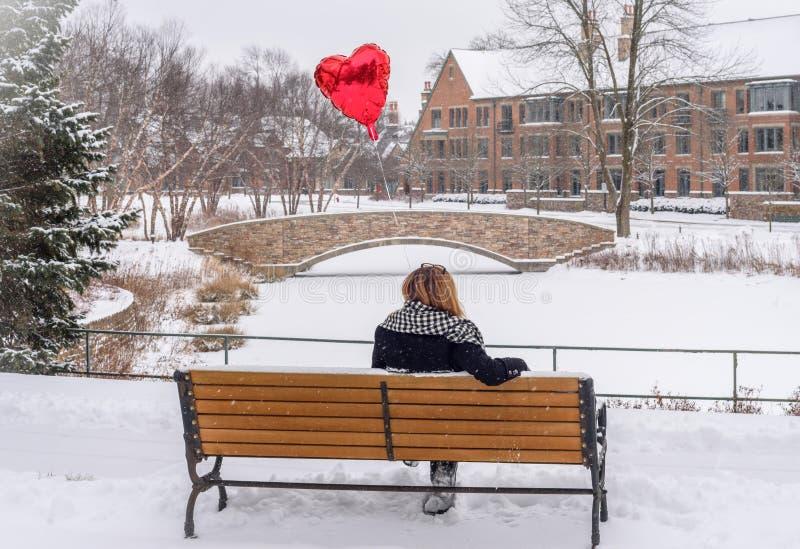 kvinnasammanträde parkerar på bänken som rymmer på den röd hjärta formade ballongen royaltyfria bilder