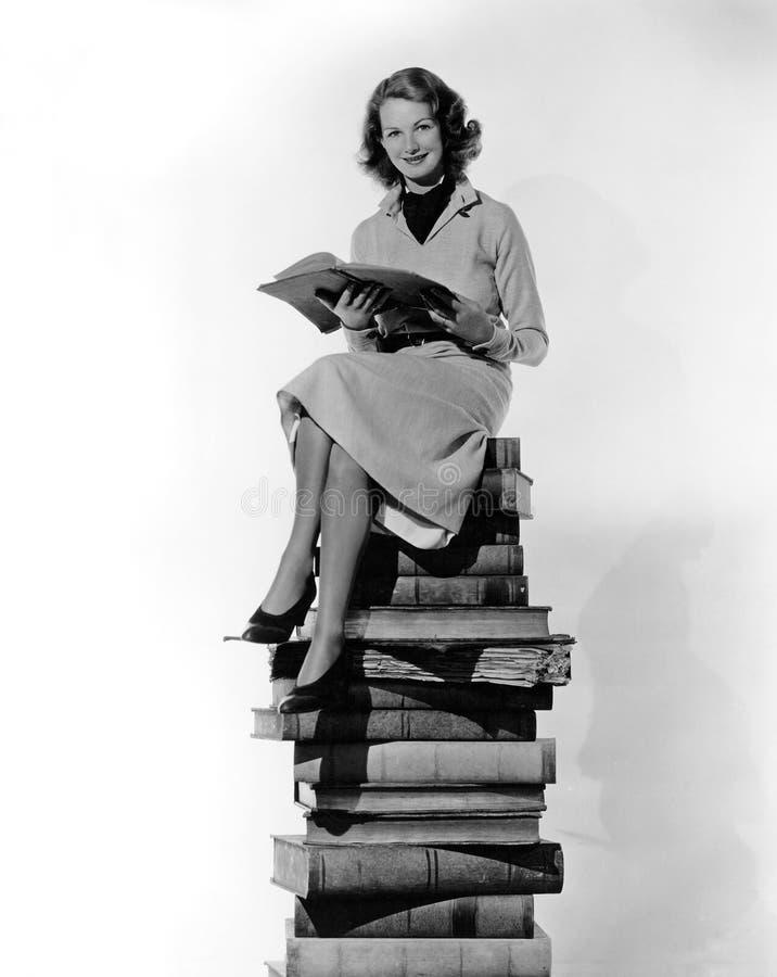 Kvinnasammanträde uppe på högen av böcker (alla visade personer inte är längre uppehälle, och inget gods finns Leverantörgarantie royaltyfria bilder