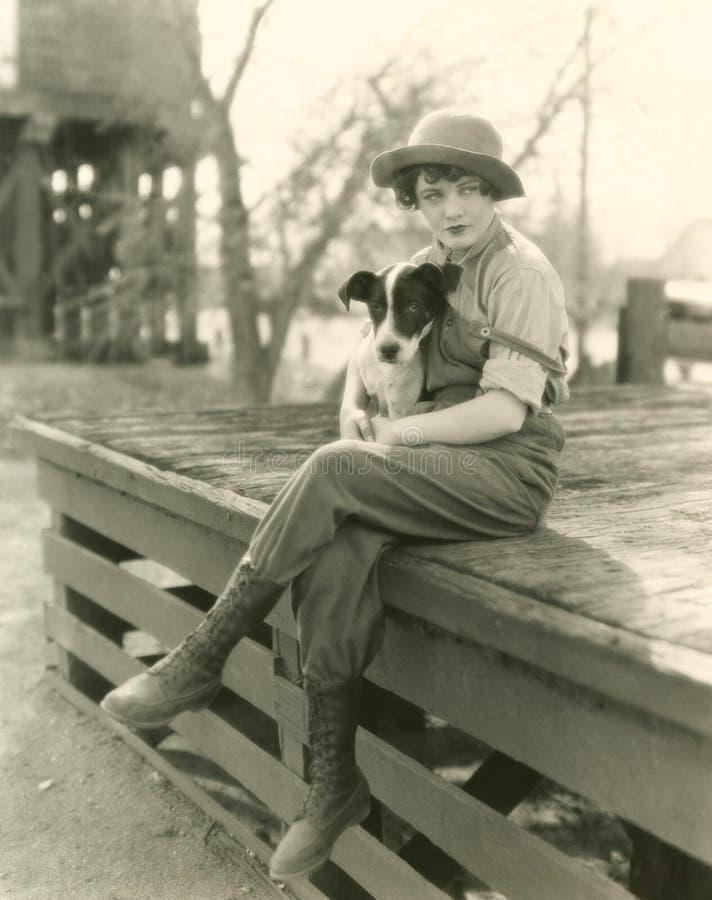 Kvinnasammanträde utomhus med hennes hund royaltyfria bilder