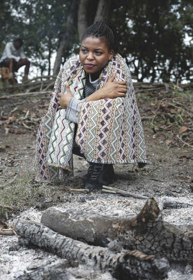 Kvinnasammanträde vid brasaaskaen royaltyfri fotografi