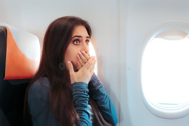 Kvinnasammanträde vid fönstret på ett flygplan som känner sig sjukt royaltyfria bilder