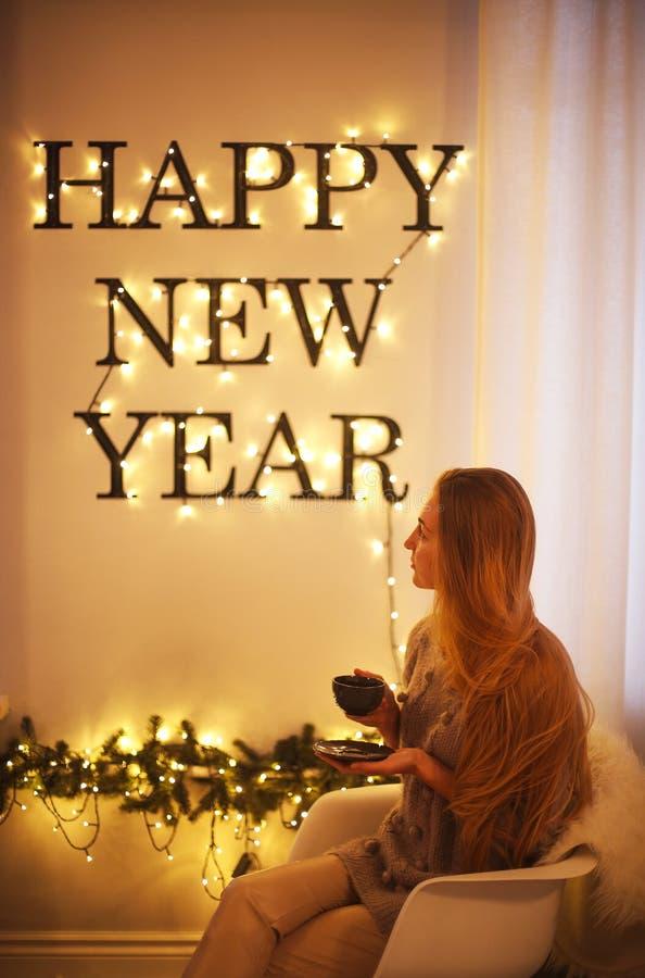 Kvinnasammanträde vid feriebokstäverna för lyckligt nytt år Ljust ord fotografering för bildbyråer