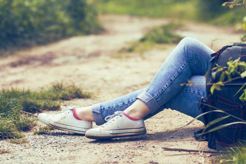 Kvinnasammanträde vid grusvägen, i jeans och vita kanfasgymnastikskor, ryggsäck vid hennes sida royaltyfri foto