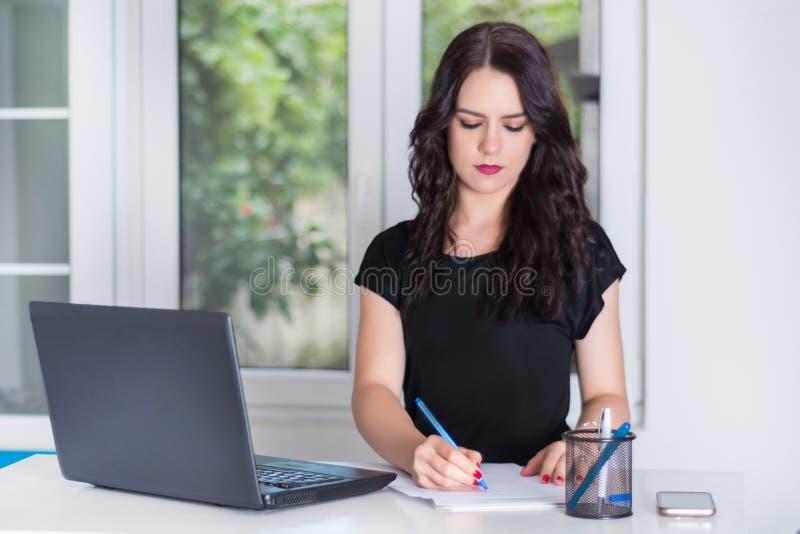 Kvinnasekreterarehandstil i anteckningsbok på skrivbordet med bärbara datorn i modernt kontor arkivfoto