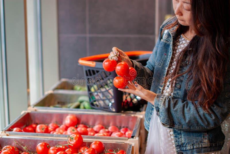 Kvinnashopping för frukter och grönsaker i jordbruksprodukteravdelning av en livsmedelsbutik/en supermarket arkivbilder