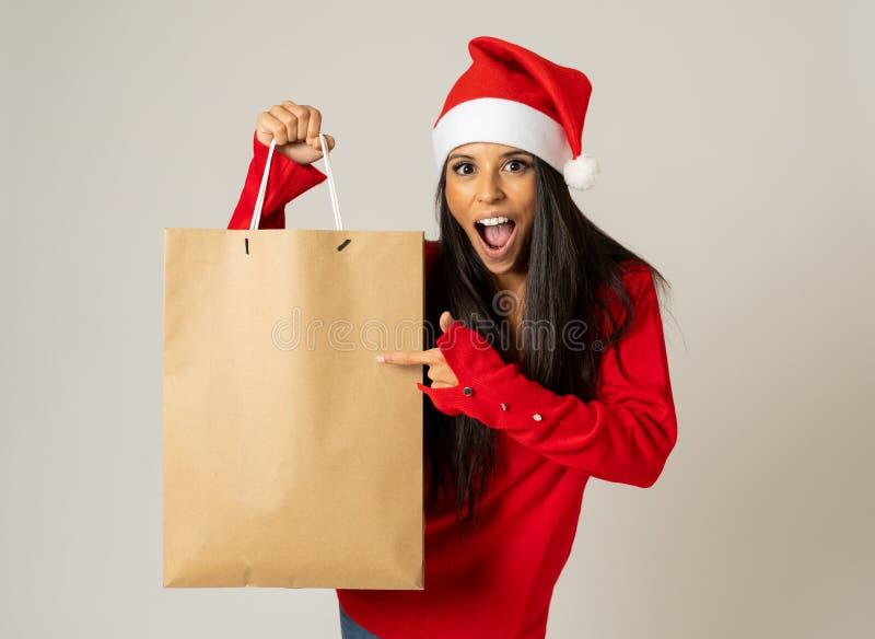 Kvinnashopping för julgåvor med shoppingpåsar och den santa hatten som ser upphetsad och lycklig fotografering för bildbyråer