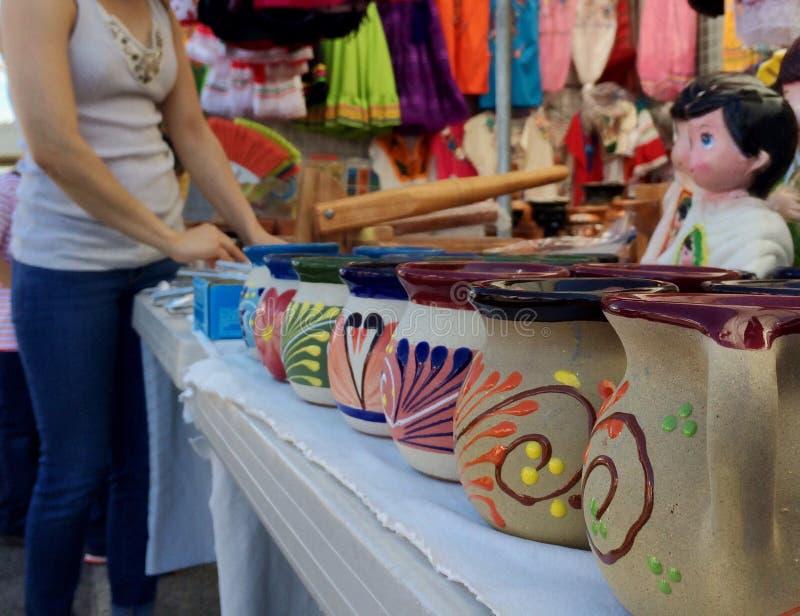 Kvinnashopping för mexicanskt handgjort hantverk på en loppmarknad royaltyfri foto