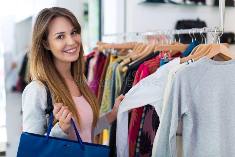 Kvinnashopping i en boutique royaltyfri foto