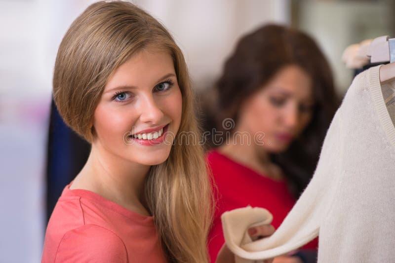 Kvinnashopping i kläderlager royaltyfri fotografi