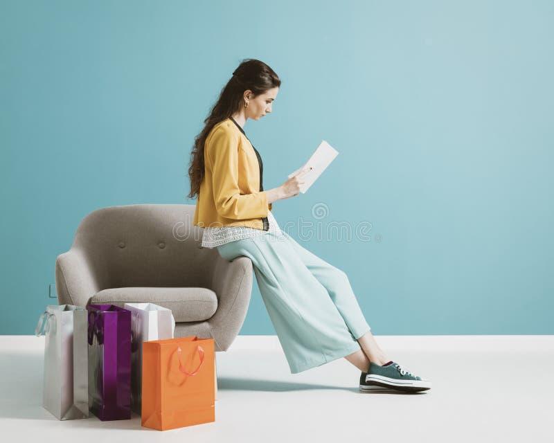 Kvinnashopping och läsa en modetidskrift royaltyfri fotografi