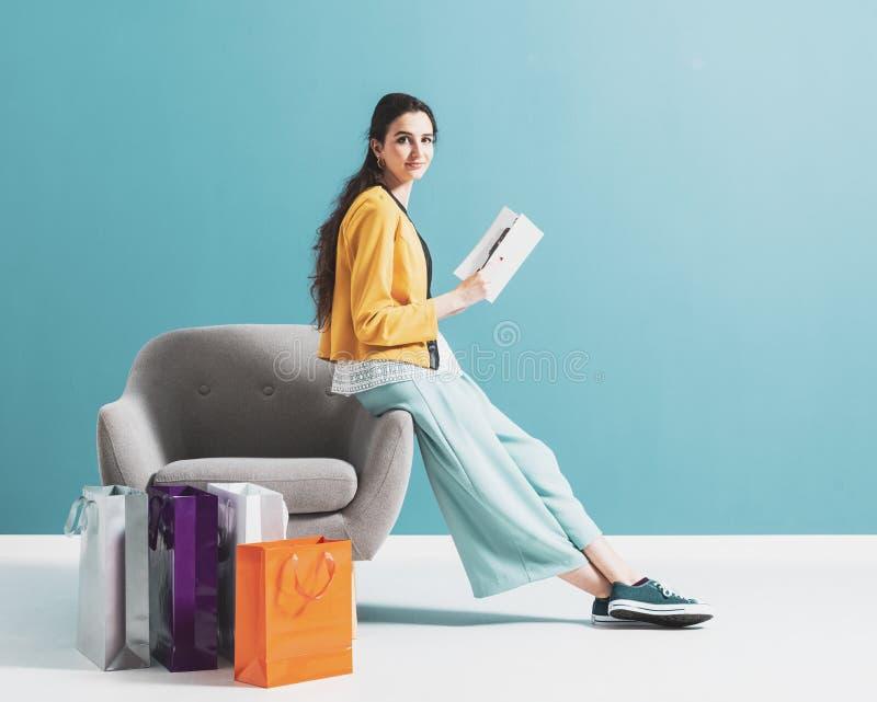 Kvinnashopping och läsa en modetidskrift arkivfoto