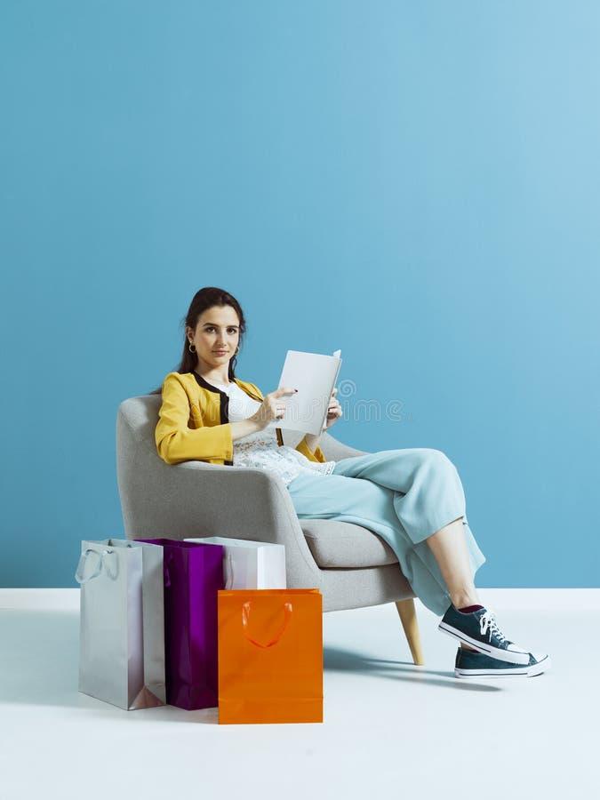 Kvinnashopping och läsa en modetidskrift royaltyfria bilder