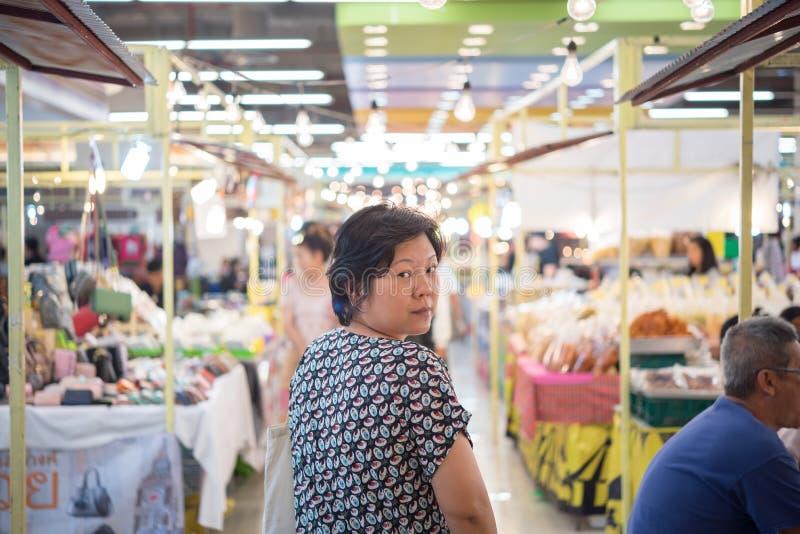 Kvinnashopping på den thailändska gatamatmarknaden royaltyfria bilder