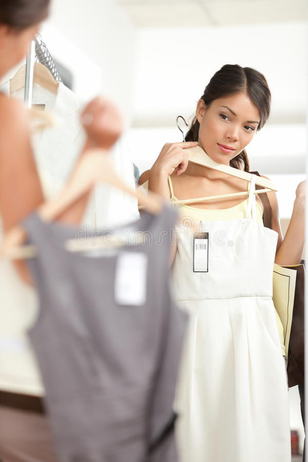 Kvinnashopping som väljer klänningar fotografering för bildbyråer
