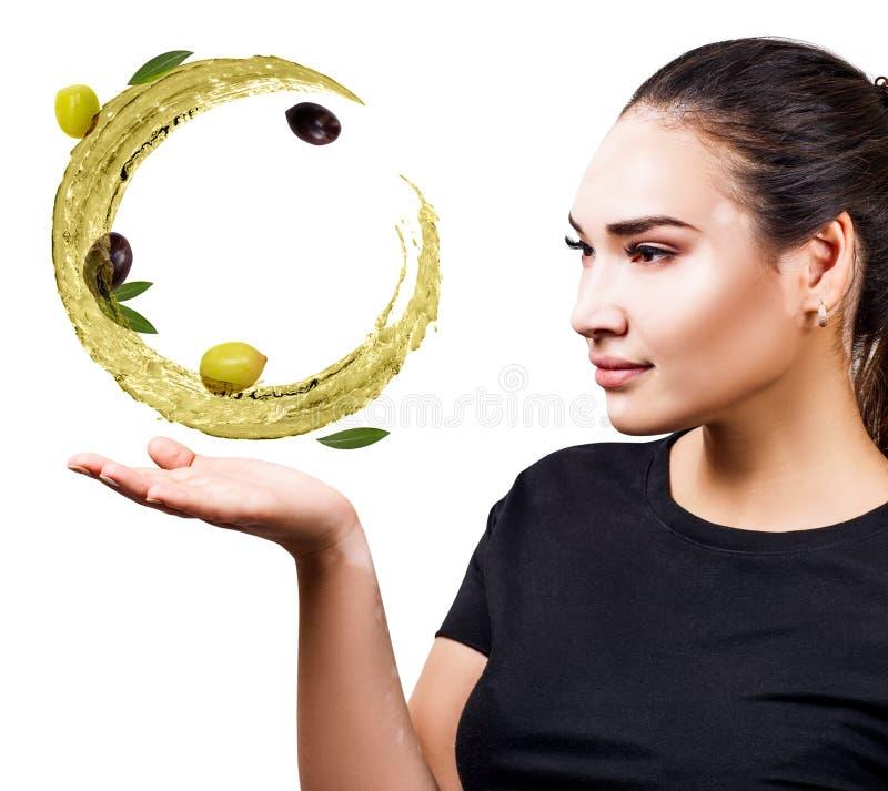 Kvinnashower cirkulerar f?rgst?nk av olivolja med oliv i hand arkivbild