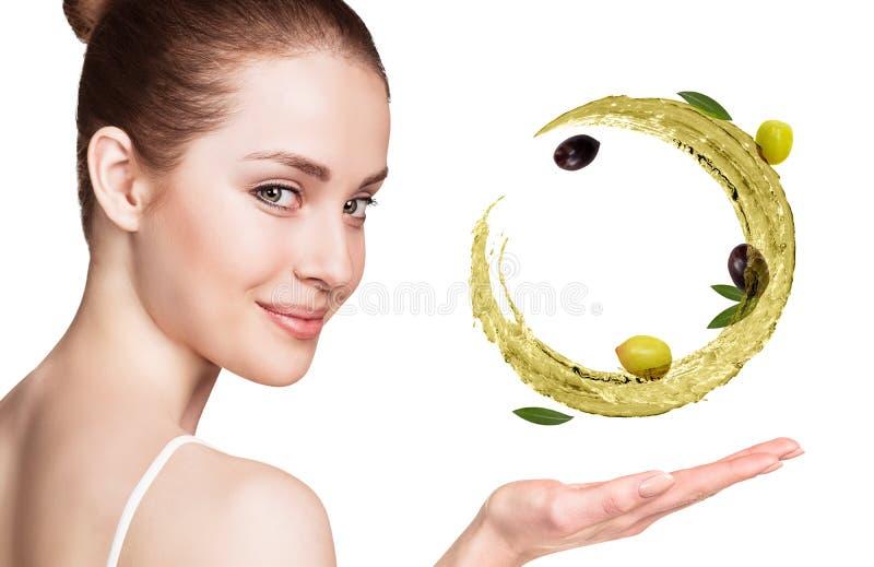 Kvinnashower cirkulerar f?rgst?nk av olivolja med oliv i hand royaltyfri foto