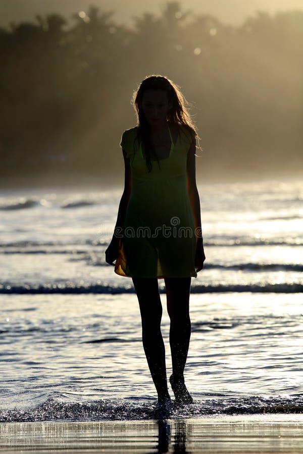 Kvinnasilhouette vid solnedgång royaltyfri bild