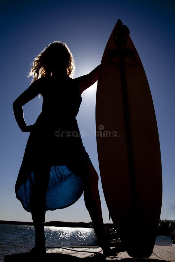 Kvinnasilhouettestand vid surfingbrädan royaltyfria bilder