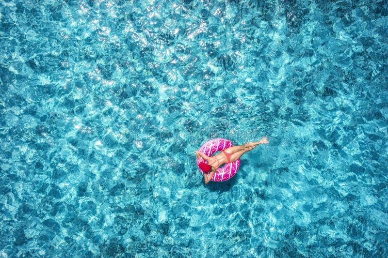 Kvinnasimning på den rosa munkbadcirkeln i det blåa havet flyg- sikt royaltyfri foto