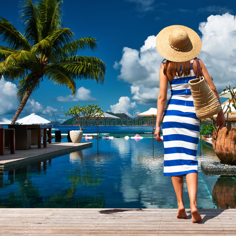 Kvinnasjöman som göras randig i klänning nära poolside arkivfoton