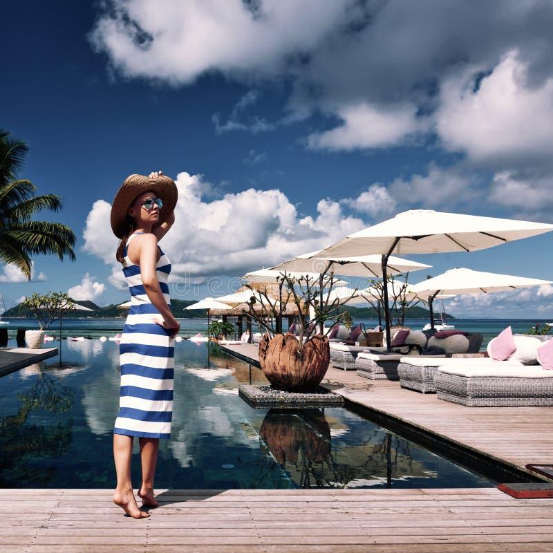 Kvinnasjöman som göras randig i klänning nära poolside royaltyfri fotografi