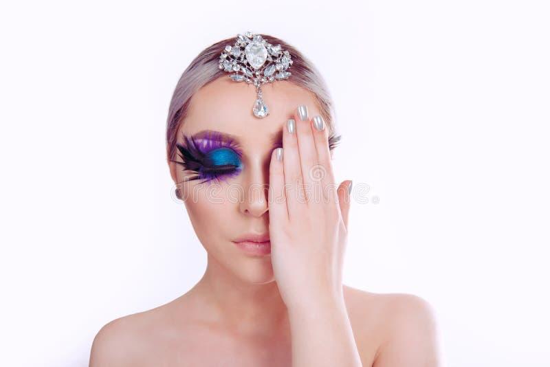 Kvinnaskönhet med den konstnärliga purpurfärgade makeupfjädern för blåa ögon på ögonfranssilversmycken på halv framsida för head  royaltyfri foto