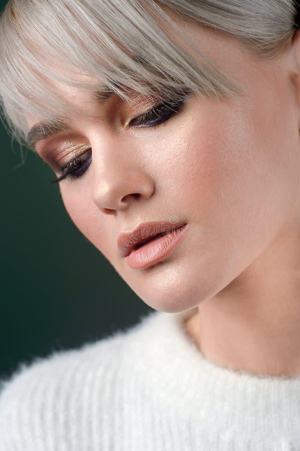 Kvinnaskönhetframsida Härlig makeup för modemodell Ung flickamakeup och smycken på blå bakgrund royaltyfri foto