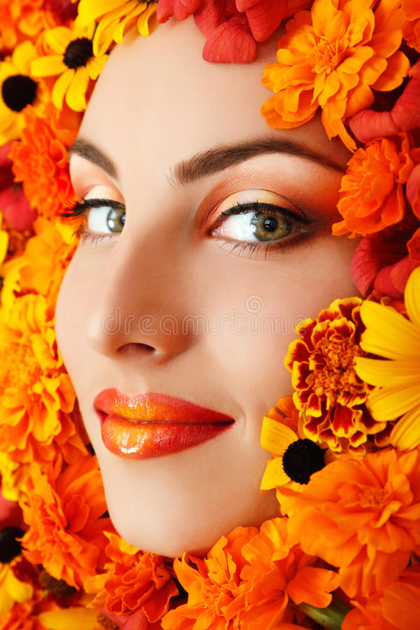 Kvinnaskönhetframsida med orange blommor royaltyfri fotografi
