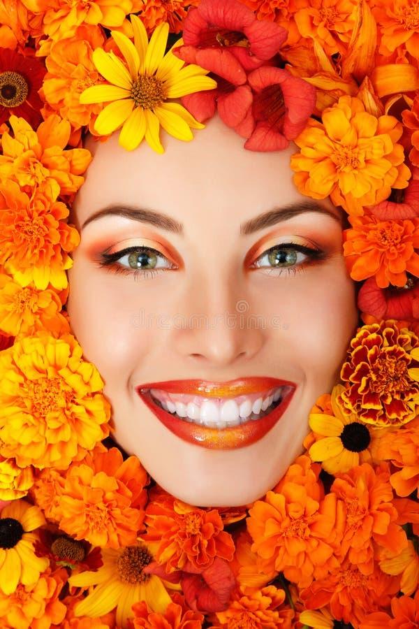 Kvinnaskönhetframsida med orange blommor royaltyfria bilder