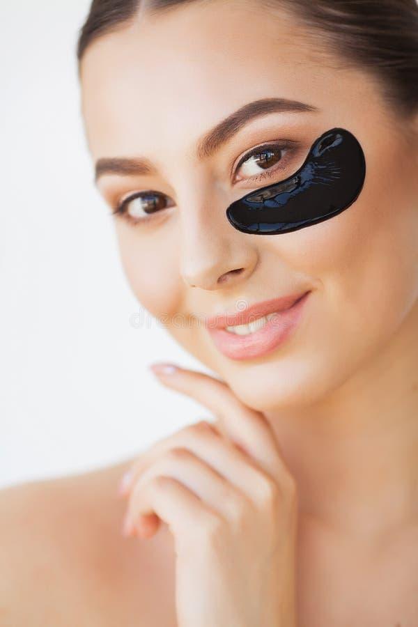 Kvinnask?nhetframsida med maskeringen under ?gon Härlig kvinnlig med naturlig makeup och svarta Collagenlappar på ny ansiktsbehan arkivbilder