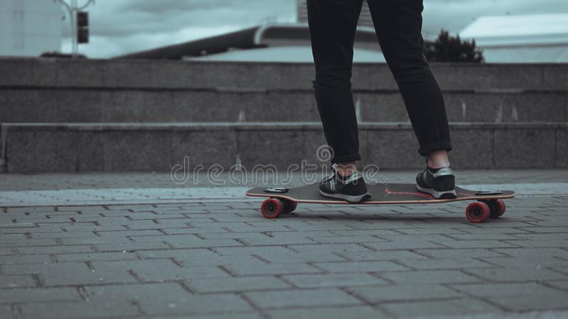 Kvinnaskateboarderben som skateboarding p? staden royaltyfri fotografi