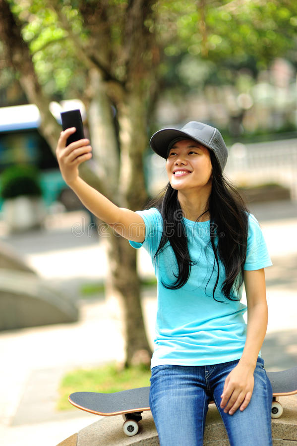 Kvinnaskateboarderen sitter använder hennes mobiltelefon royaltyfri fotografi