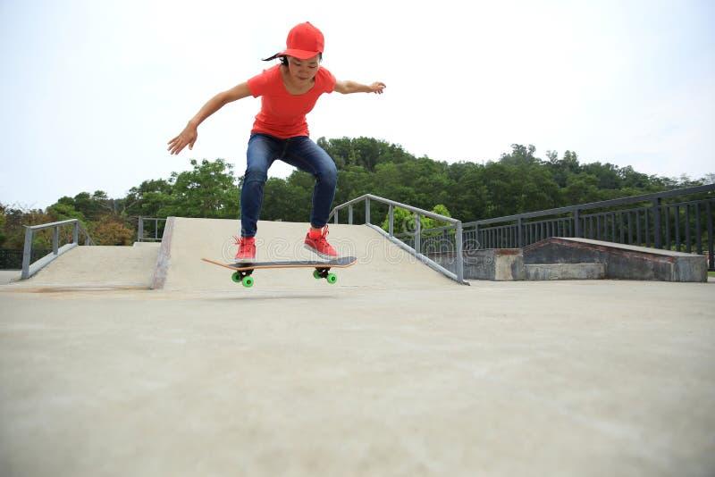 Kvinnaskateboarderen som skateboarding på skridskon, parkerar royaltyfri fotografi