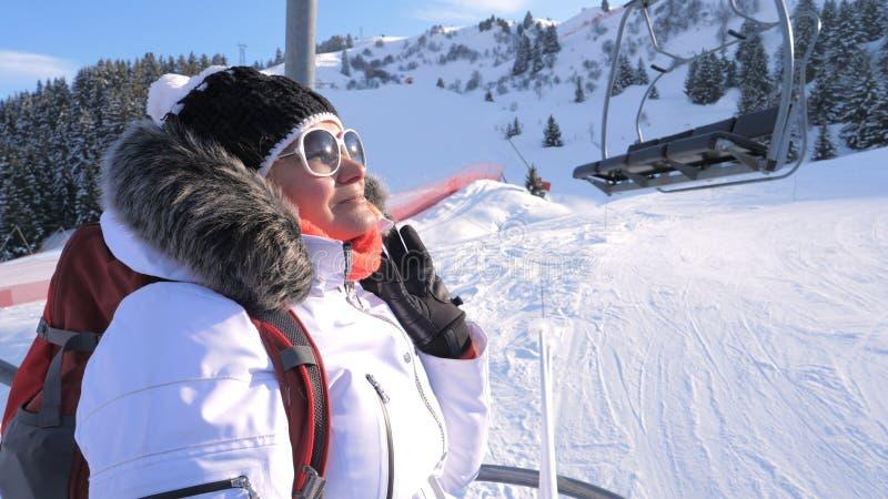 Kvinnaskidåkareklättringar en stol lyfter upp ett berg i en skidasemesterort royaltyfria foton