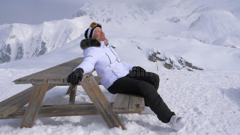 Kvinnaskidåkarenöje att koppla av i bergen på en Sunny Day Sitting på bänk arkivbild