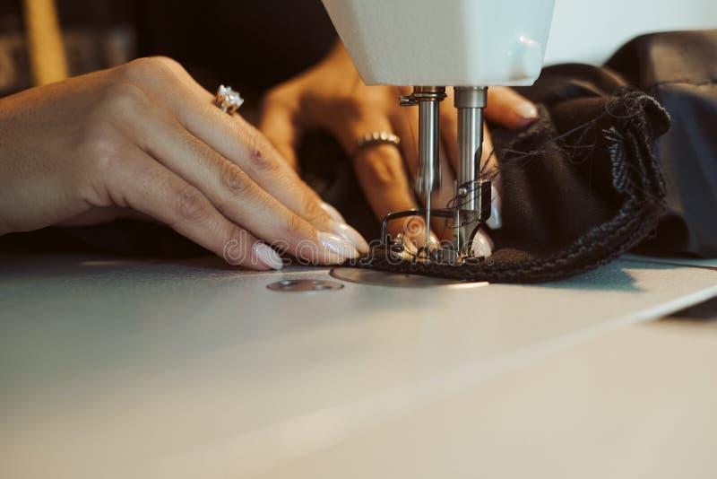 Kvinnaskräddarehänder som arbetar på symaskinen arkivbild