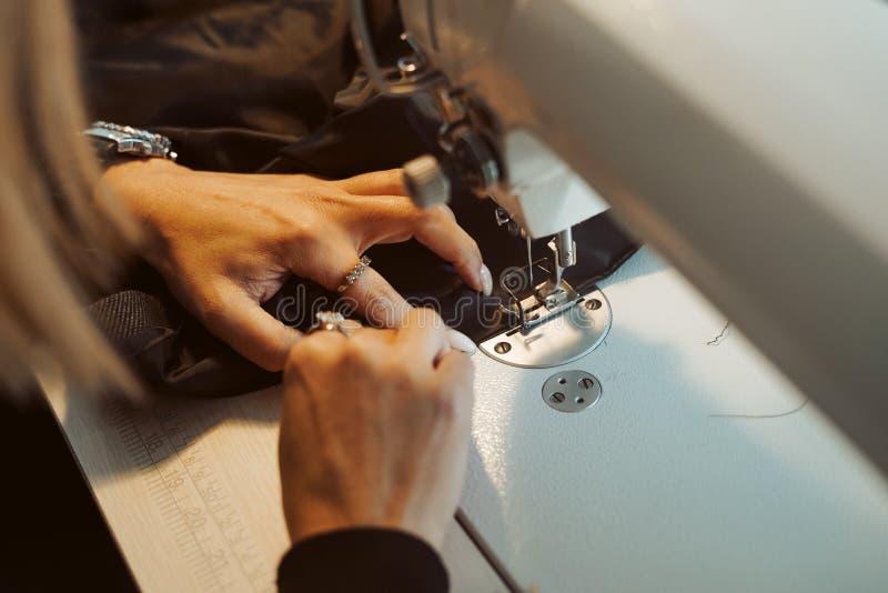 Kvinnaskräddarehänder som arbetar på symaskinen royaltyfria foton