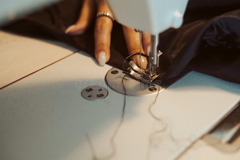 Kvinnaskräddarehänder som arbetar på symaskinen arkivbilder