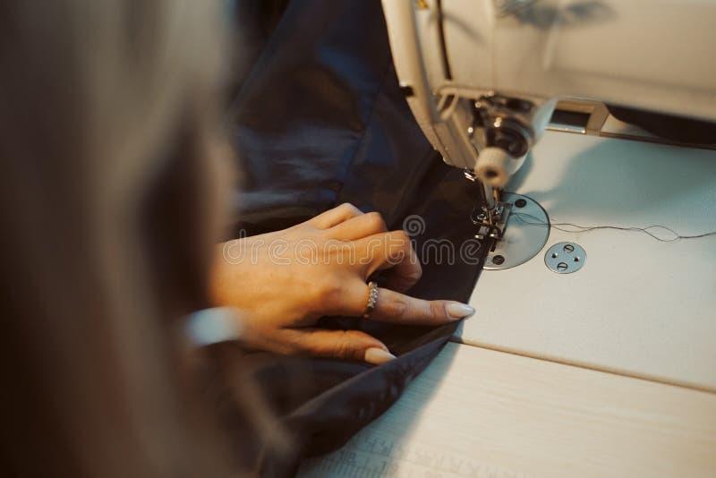 Kvinnaskräddarehänder som arbetar på symaskinen royaltyfri foto