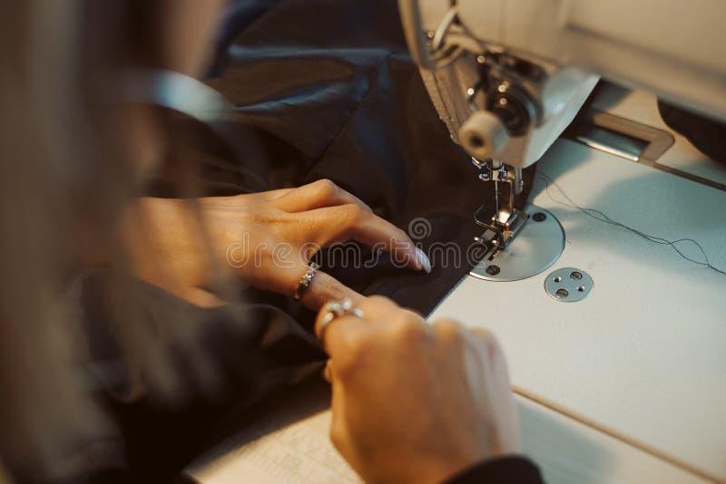 Kvinnaskräddarehänder som arbetar på symaskinen royaltyfria bilder