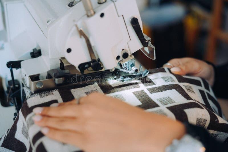 Kvinnaskräddarehänder som arbetar på symaskinen arkivfoton