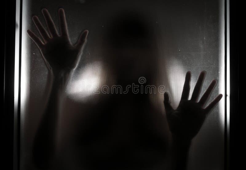 Kvinnaskugga bak den genomskinliga spegeln royaltyfri bild