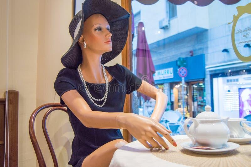 Kvinnaskyltdocka i elegant hatt och klänningen som sitter på kafétabellen i fönstret, Cagliari, Sardinia, Italien-Oktober 09, 201 arkivfoto