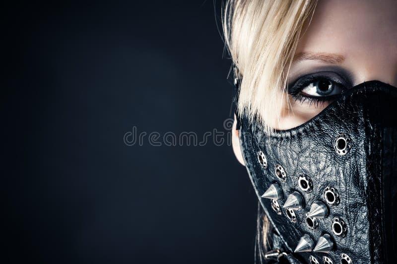 Kvinnaslav i en maskering med grova spikar arkivfoto