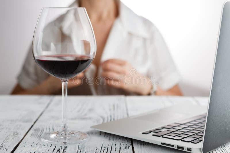 Kvinnaslut av arbeten med exponeringsglas av den rött vinminnestavlan och bärbara datorn arkivfoton